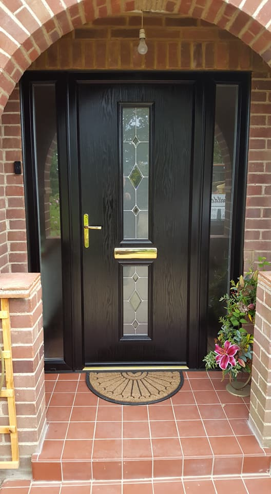 Remove old front door, enlarge opening, lay soldier course of bricks across the top and new door with sidelights fitted.