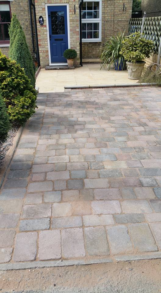Dig out existing driveway and paved area, new paving slabs laid on lower level with rustic block pavers to top section.